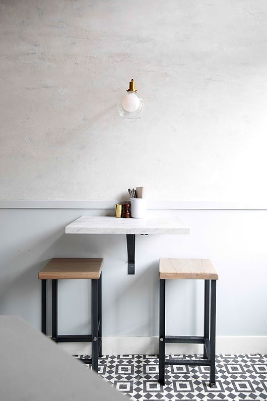 white marble mounted table, white wall, wooden stools with black metal, black and white patterned floor tiles