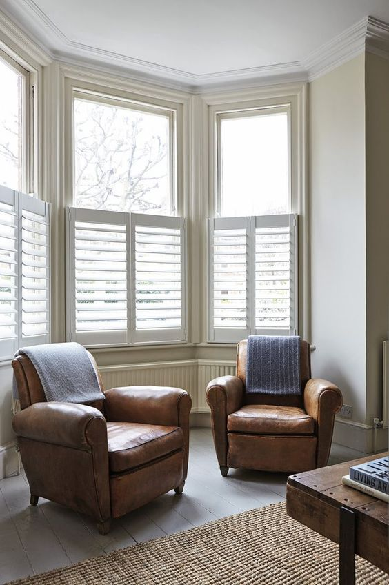 white window shutters, white wall, brown leather chairs, white wooden floor, rattan rug, wooden table