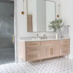 Wooden Bathroom Vanity In Light Brown, White Wall, White Patterned Floor Tiles, White Marble Counter Top, Large Square Mirror, Golden Glass Sconces