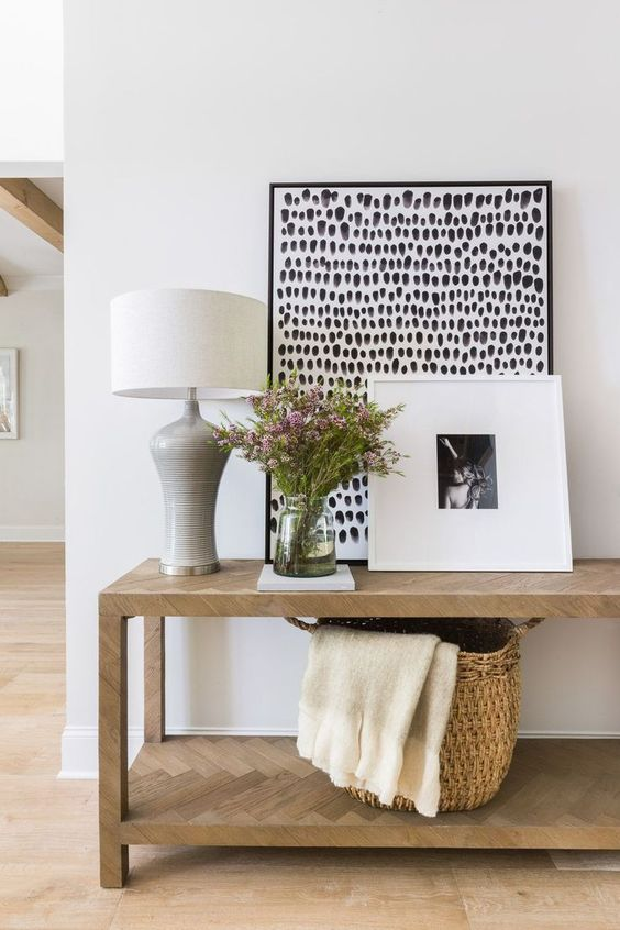 wooden console table with herringbone pattern, white wall, wooden floor, white table lamp