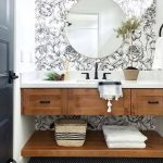 Wooden Floating Vanity With White Counter Top, Floating Wooden Shelves, White Wall, White Patterned Accent Wall, Round Mirror