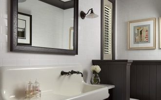 bathroom, brick herringbone floor, white wall tiles, black wainscoting, dark brown cabinet, white long sink, white toilet, black pendant, black framed mirror