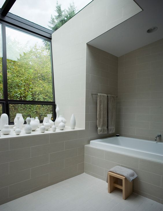 bathroom, cream subway wall, cream floor, glass ceiling, glass window, tub with white inseide