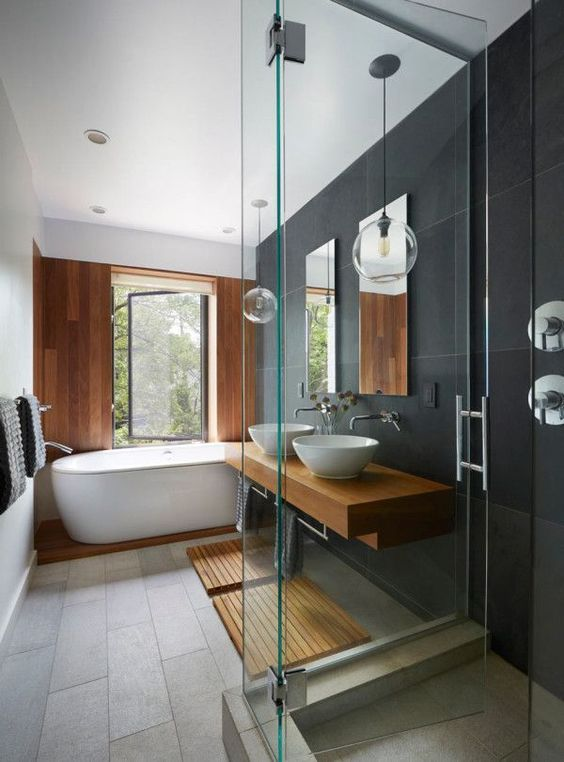 bathroom, grey floor, dark grey accent wall, mirrors, glass bulb pendants, glass partition, white tub, wooden wall