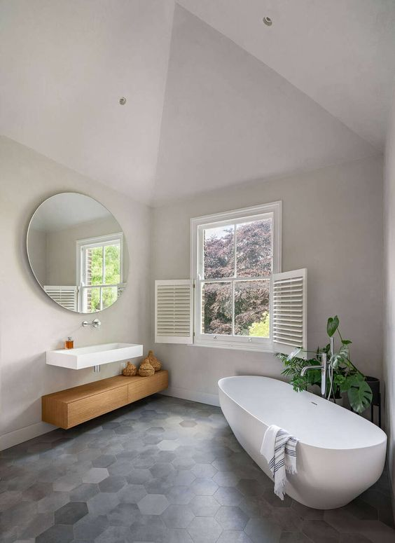 bathroom, grey hexagonal floor tiles, grey wall, vaulted ceiling, round mirror, white wooden window, white floating sink, wooden floating cabinet, white tub