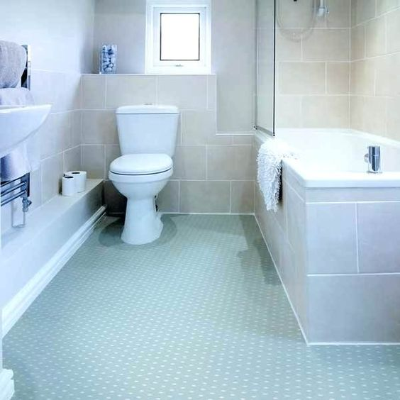 bathroom, light blue rubber flooring, brown wall tiles, white wall, white tub, white toilet