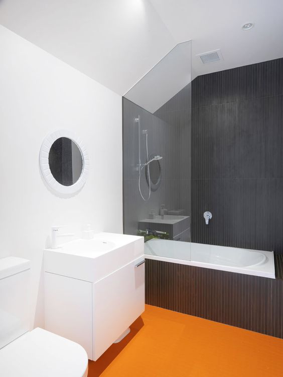 bathroom, orange rubber flooring, white wall, black tub area, black wall tub area, glass partition, white vanity, white toilet