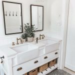 Bathroom, Patterned Floor Tiles, White Wall, White Wooden Vanity, White Drawers, White Apron Sink, White Wainscoting, Black Framed Mirror, Glass Sconces