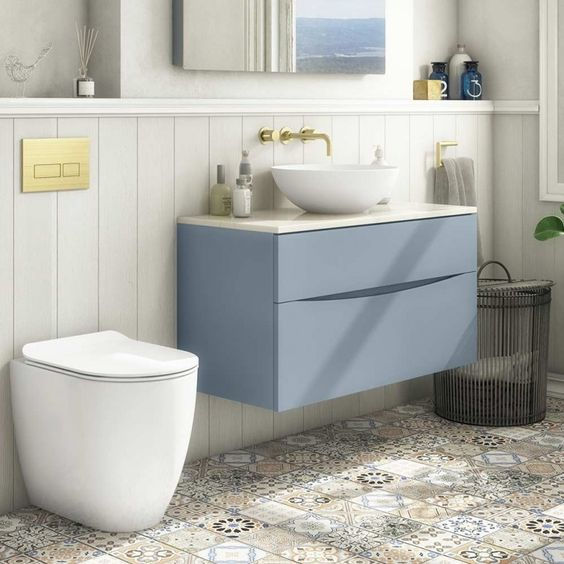bathroom, patterned floor, white wooden wainsocting, cream wall, mirror, blue floating cabinet, white counter top, white bowl sink, white toilet