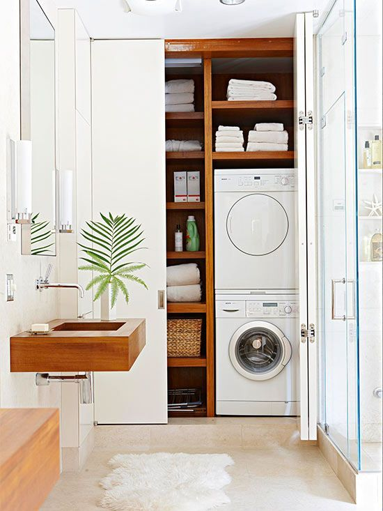 bathroom, white floor, white wall, white cupboard with shelves and laundry machines, floating wooden sink, mirror, glass partition