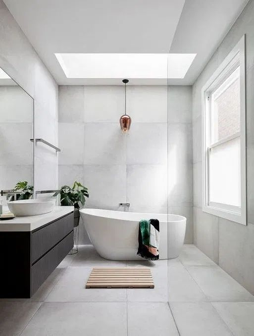 bathroom, white floor, white wall, white tub, black floating cabinet, white counter top, white sink, glass ceiling window, golden pendant