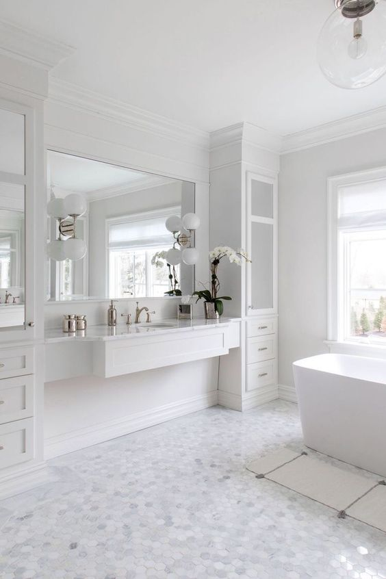 bathroom, white hexagonal floor tiles, white tub, white floating vanity, white cupboard, clear glass pendant, white sonces