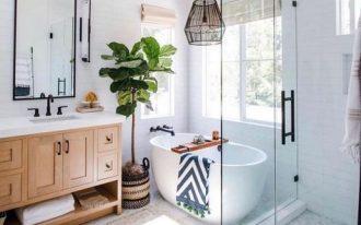 bathroom, white hexagonal tiny floor tiles, white square wall tiles, wooden cabinet, white tub, black iro pendant, glass partition, large mirror