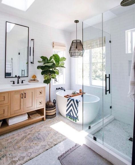 bathroom, white hexagonal tiny floor tiles, white square wall tiles, wooden cabinet, white tub, black iro pendant, glass partition, large mirror