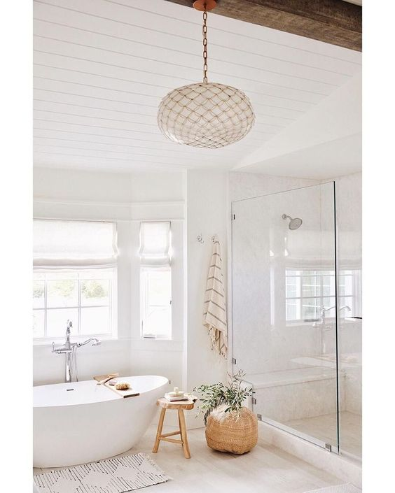 bathroom, white marble floor, white planks on ceiling, glass partition, white tub, white pendant, window