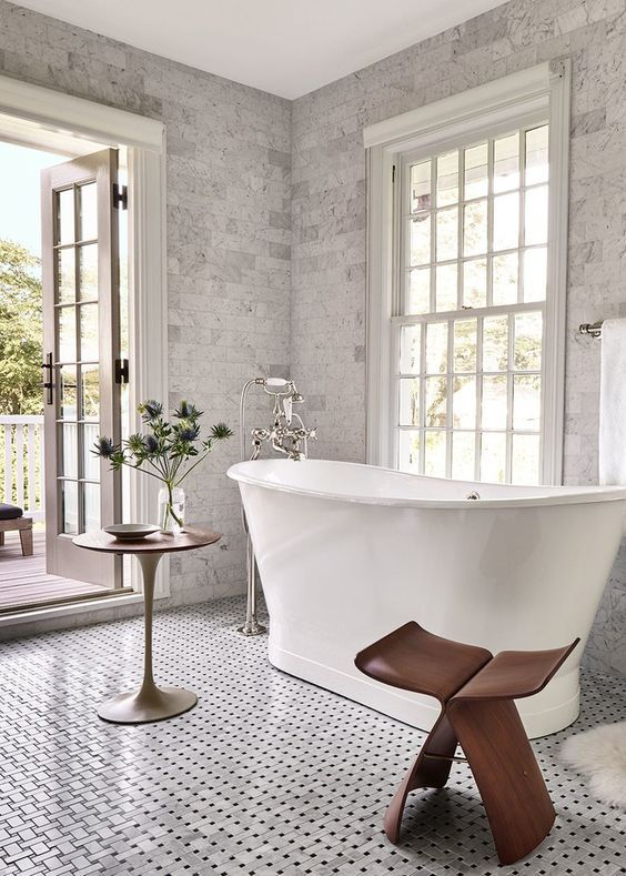 bathroom, white patterned floor, white tub, grey wall tiles, round side table, glass window, glass door