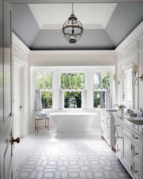 bathroom, white patterned floor, white wall, white tub, grey vaulted ceiling, glass globe pendant, white cabinet, windows with curtain