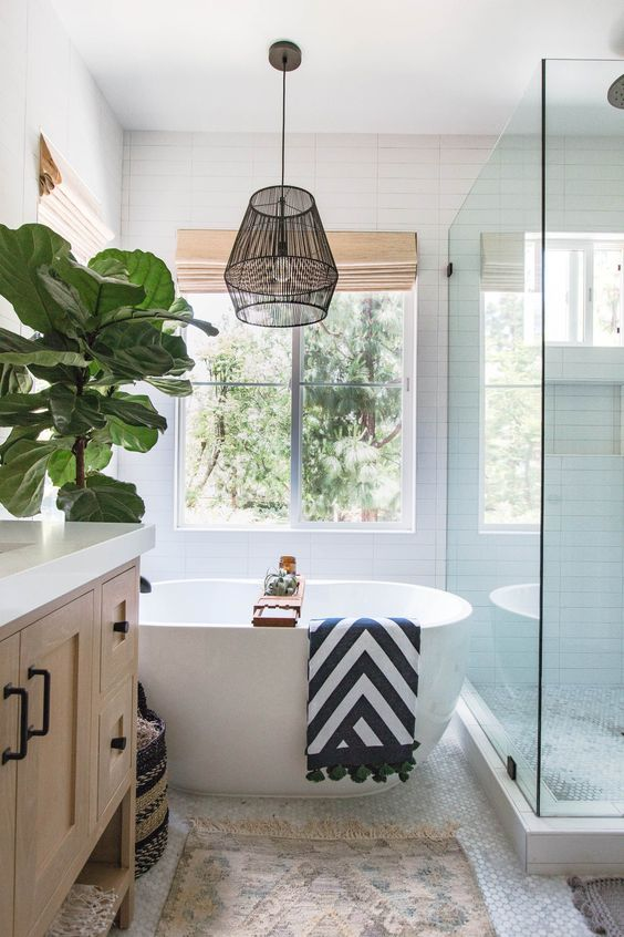 bathroom, white subway wall, glass partition, white tub, white tiny hexagonal floor tiles, wooden vanity, black metal pendant