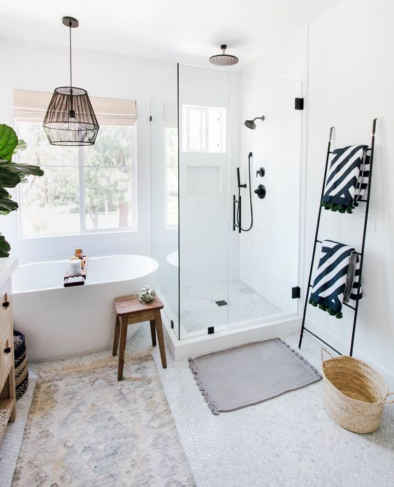bathroom, white tiny hexagonal floor tiles, white wall, glass partition, white tub, black iron cage pendant, wooden stool, black rack