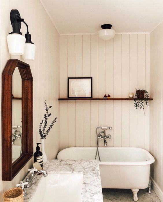 bathroom, white vertical planks, white marble vanity top, white marble floor, dark wooden framed mirror, white sconces, floatig wooden shelves, white tub with white claw feet
