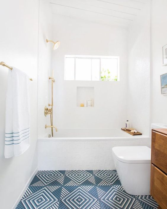 bathroom, white wall, white toilet, white tub, golden faucet, wooden cabinet, blue patterned floor