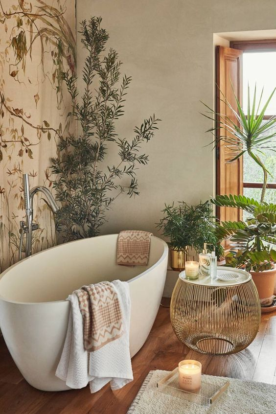 bathroom, wooden floor, cream wall, wallpaper, white tub, rattan round coffee table, plants