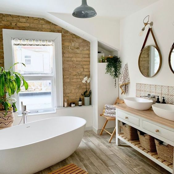 bathroom, wooden tiles, brick wall, white wall, window, round mirror, wooden vanity table, white sinks, white tub