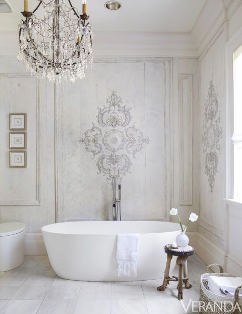 batroom, white wooden floor, white wall with details, white tub, white toilet, crystal chandelier