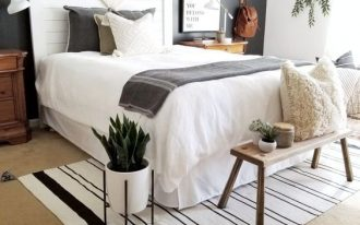 bedroom, brown rug floor, white wall, black wall, white headboard, wooden bench, wooden bedside cabinet,