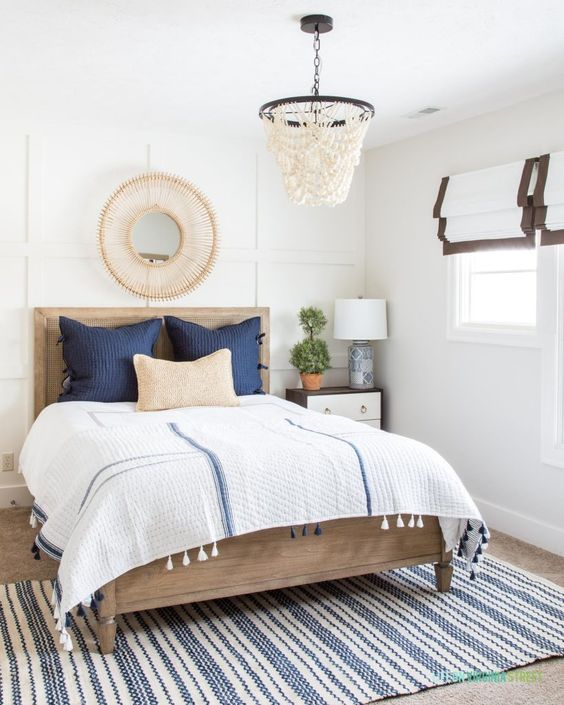 bedroom, brown rug floor, white wall, white table lamp, side cabinet, white macrame pendant, wooden bed platform, white bedding
