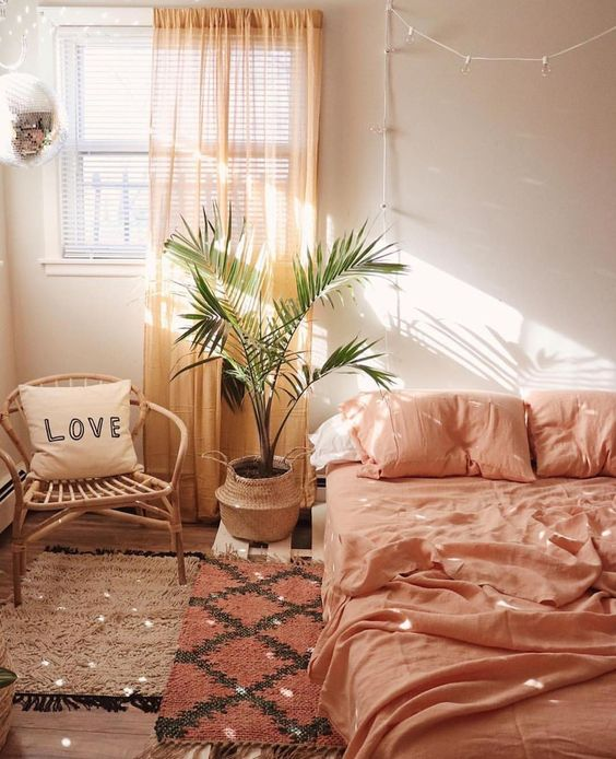 bedroom, brown rug, red rug, pink bedding, white wall, orange curtain, rattan chair, plants