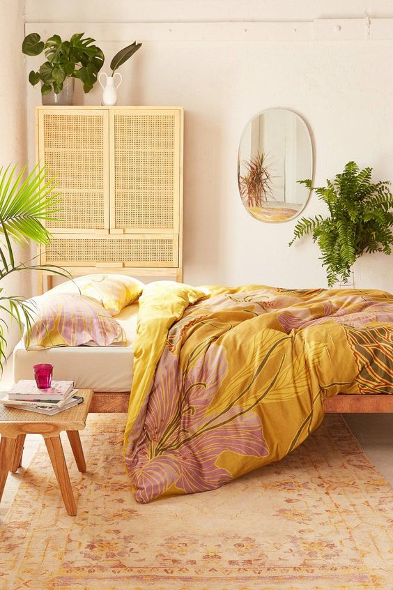 bedroom, orange rug, white wall, rattan cupboard, wooden platform, yellow bedding, wooden side table, mirror