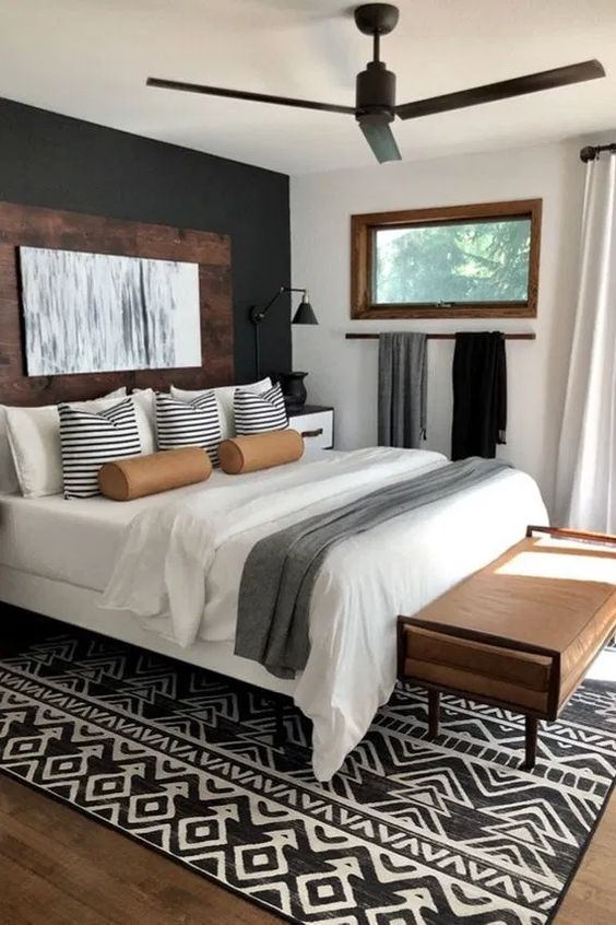 bedroom, wooden floor, white wall, black accent wall, white bed platform, brown leather bench, black ceiling fan