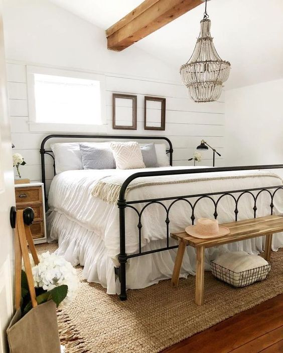 bedroom, wooden floor, wooden bench, black metal bed, white shiplap wall, white ceiling, crystal chandelier, rattan rug
