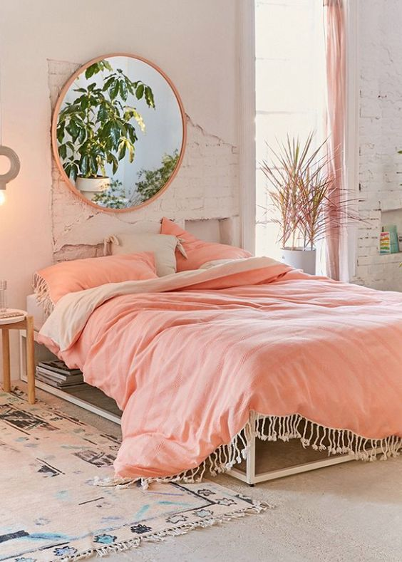 bohemian bedroom, peach bedding, cream platform, rug, pink round mirror, peach curtain, white exposed wall