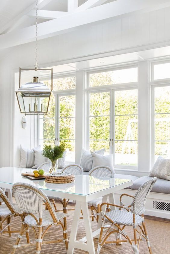 breakfast nook, wooden floor, white wall, white bench, grey cushion, white pillows, white rattan chairs, white table, golden framed pendant