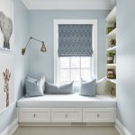 Children's Bedroom, Brown Rug, Light Blue Wall, White Bench With Drawers, Shelves, Golden Sconces, Blue Patterned Curtain, White Cushion