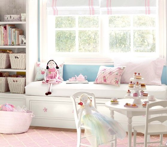 children's bedroom, pink rug, white built in bench, white cushion, white shelves, pillows, low tables and chairs