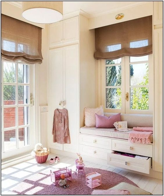 children's bedroom, white window seat with drawers, white wooden floor, pink rug, white cupboard, brown shade, round brown pendant