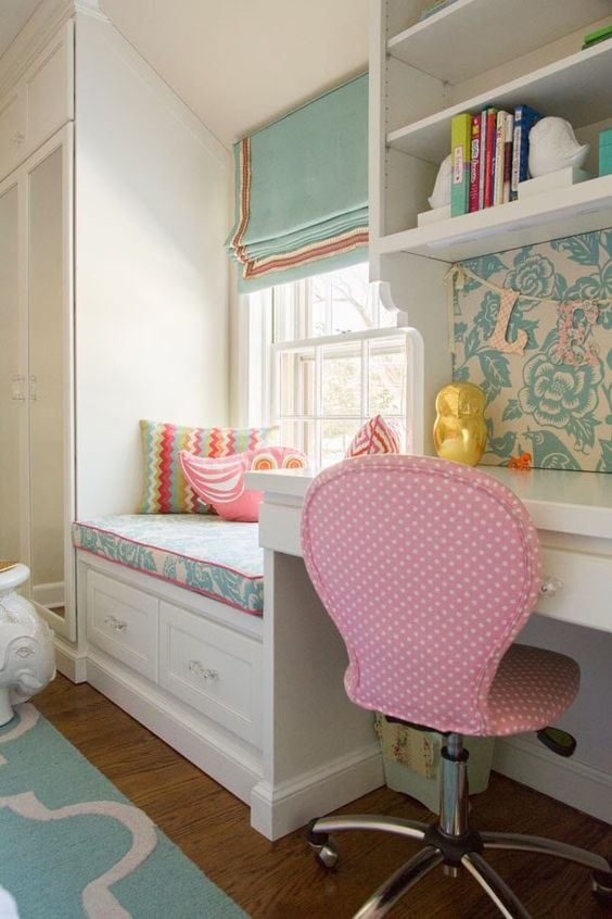 children's bedroom, wooden floor, turquoise rug, pink office chair, white bench with drawers, white cupboard, white framed window, white study table, white shelves
