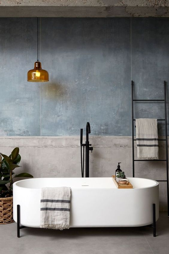 concrete floor, grey wall, golden pendant, white long tub, black faucet, black rack