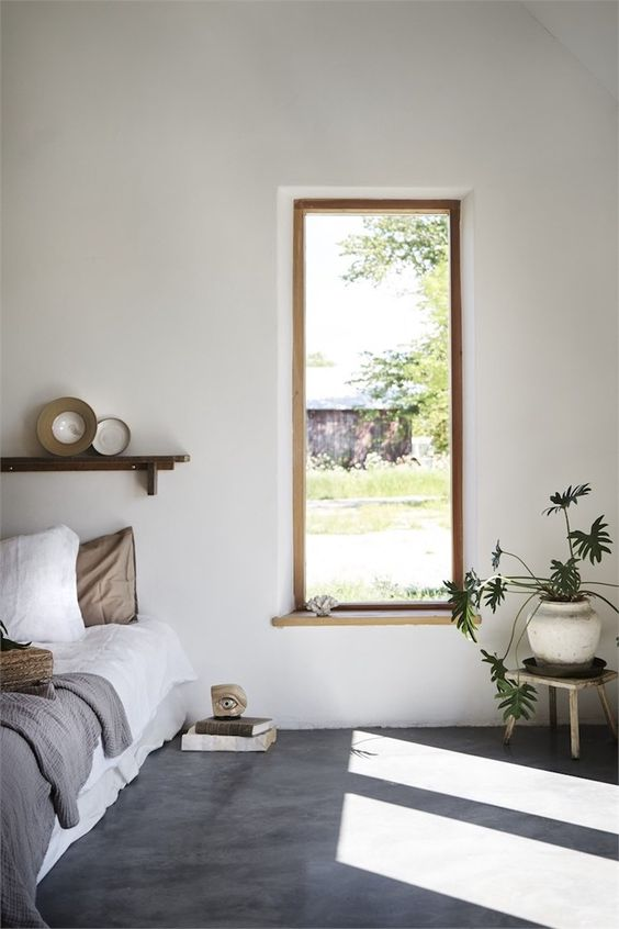 concrete floor, white wall, wooden framed window, white bedding, floating wooden shelves