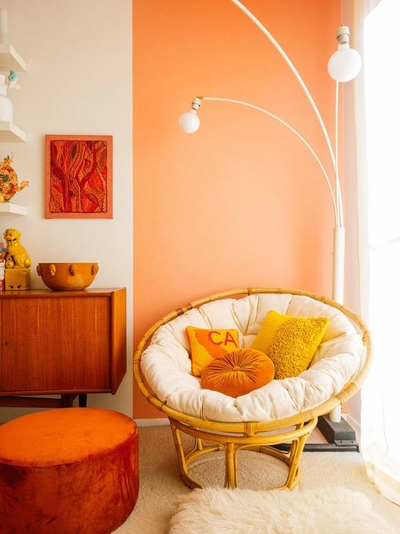 corner room, white orange wall, white bulb floor lamps, rattan chair, brown rug, orange ottoman, wooden cabinet