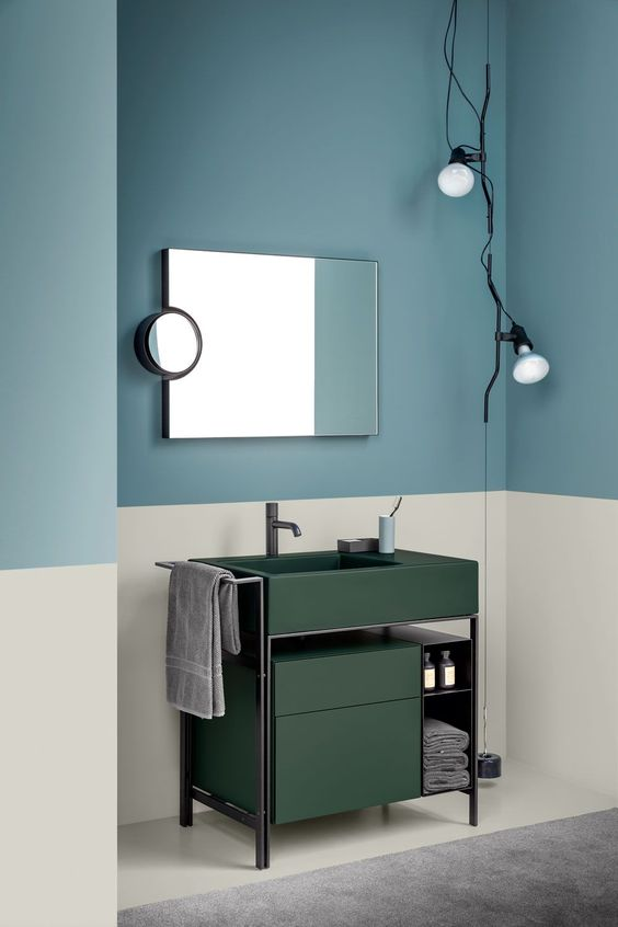 cream wall, soft navy wall, dark green vanity, grey floor