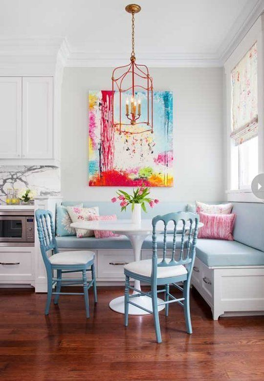 dining nook, wooden floor, white wall, white bench, blue cushion, blue chair with shite cushion, red framed pendant, white tulip table