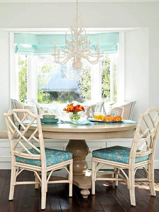 dining nook, wooden floor, white wall, white bench, white rattan chairs, white chandelier, round table, brown pillows