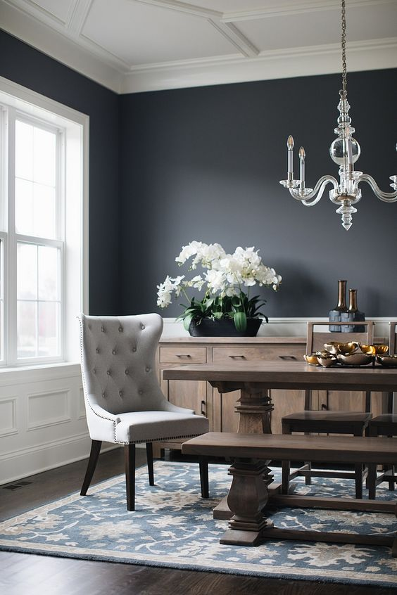 dining room, dark wooden floor, grey painted wall, white ceiling, white wainscoting, crystal chandelier, wooden table, wooden chairs, wooden bench