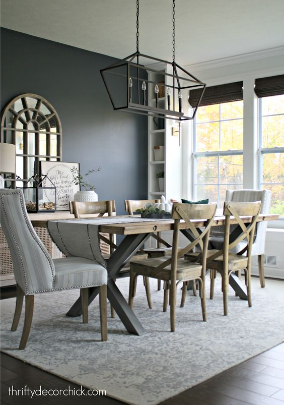 dining room, dark wooden floor, grey wall, white wall, large windows, black metal cage chandelier, wooden table, wooden chairs, whit chairs