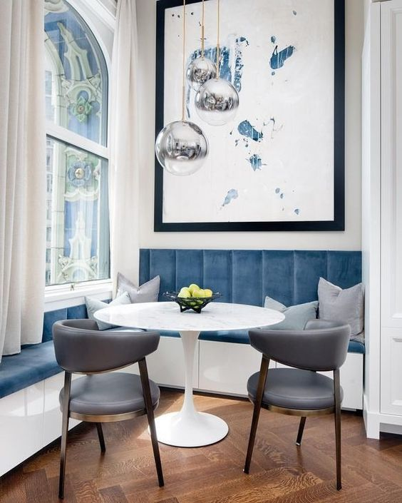dining room, herringbone floor, white wall, tall glass window, blue velvet bench, white bench, grey chairs, silvery pendant