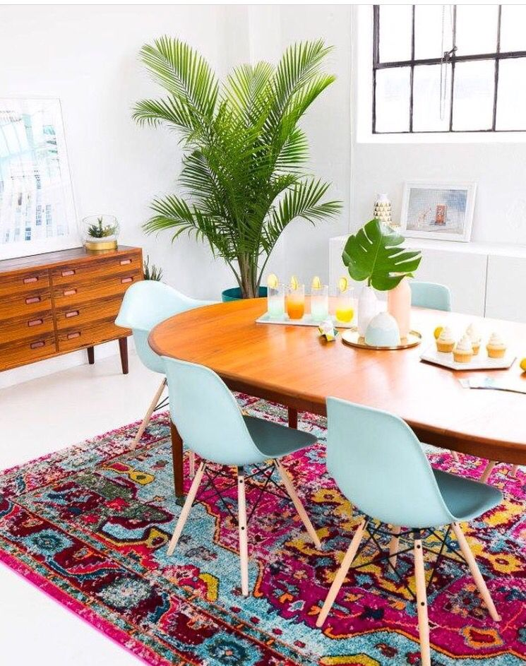 dining room, white floor, white wall, wooden oval dining table, blue midcentury modern chairs, wooden cabinet, white cabinet, plant